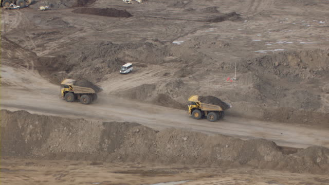 dump trucks carry oil sands through a mine in fort mcmurray, canada. - alberta stock videos & royalty-free footage