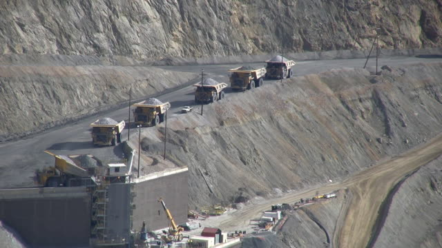 dump trucks dumping rock into in pit crusher - iron ore stock videos & royalty-free footage