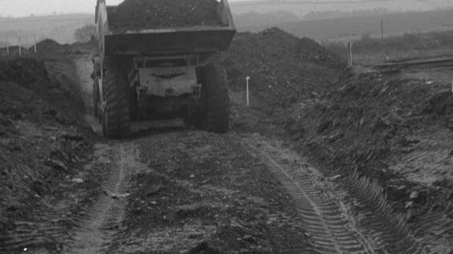1954 ts dump trucks loaded with dirt driving on rutted road with tire tracks, crossing rolling field / united kingdom - 1954 bildbanksvideor och videomaterial från bakom kulisserna