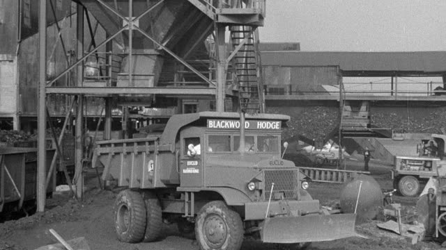 1954 montage dump trucks parked with dirt funneling down to back of trucks, trucks exiting loading area and driving over hilly, rutted terrain to disposal area / arkwright, england, united kingdom - ダンプカー点の映像素材/bロール