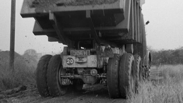 1954 montage dump trucks rolling over dirt road deeply rutted with tire tracks, twisting through bare, hilly field, with observers on platform and hills in background / united kingdom - 1954 stock videos & royalty-free footage