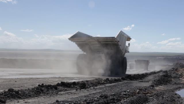 dump trucks travel through the open pit at the tavan tolgoi coal deposit developed by erdenes tavan tolgoi jsc, a unit of erdenes mongol llc in... - mongoliet bildbanksvideor och videomaterial från bakom kulisserna