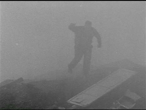 dump w/ door on ground, person running through smoke, mist, fog. smoke, mist, fog flowing into residential area, person in hardhat jumping fence,... - whatif点の映像素材/bロール