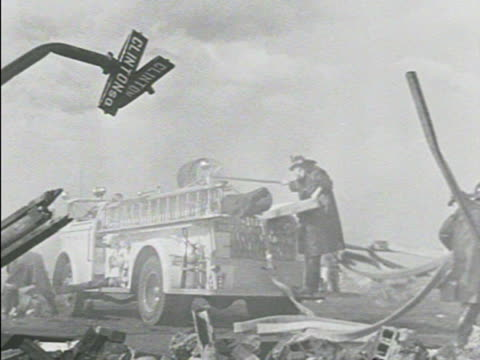 dump w/ smoke & bent street sign. fire truck pulling up, taking out hose, stepping on doll, shooting water into smoke, men in white arriving, out of... - whatif点の映像素材/bロール