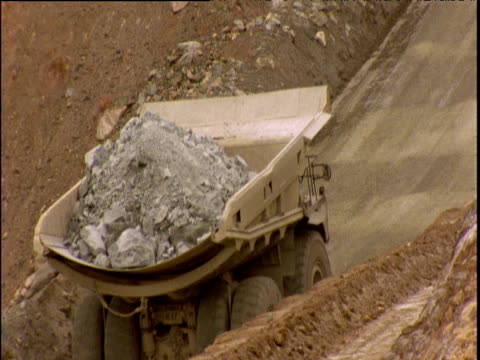 Dumper truck laden with heavy rock slowly makes way up hill in quarry Kalgoorlie Australia