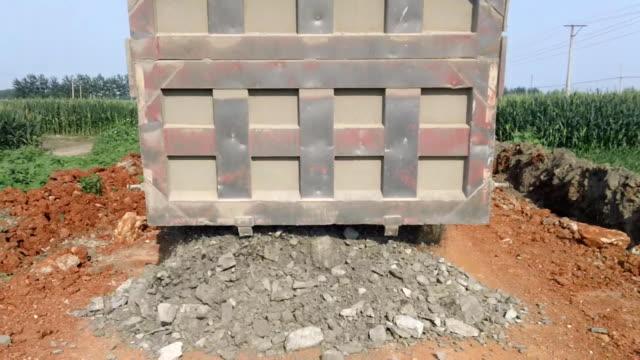 dumper unloading sand stone. - unloading stock videos & royalty-free footage