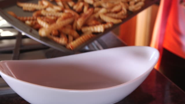 dumping potato fries into white bowl cu - wiese stock videos & royalty-free footage