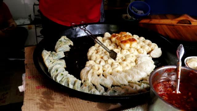 vídeos de stock, filmes e b-roll de bolinhos de cozinha sobre um prato aquecido na china - bolinho de massa