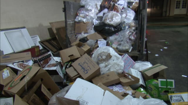 A dumpster overflows with plastic bags, cardboard and other trash.