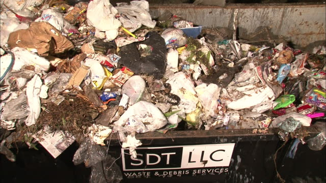 stockvideo's en b-roll-footage met a dumpster overflows with trash. - afvalcontainer container