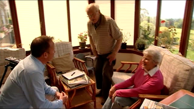 dunblane celebrates andy murray's wimbledon victory; int roy erskine and shirley erskine and reporter taking seats shirley erksine interview sot - ダンブレーン点の映像素材/bロール