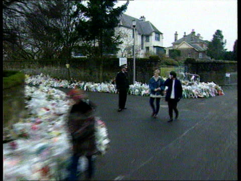 firearms amnesty announced: father's appeal:; scotland: dunblane: ext lms track forward past floral tributes lining pavement leading to school r-l as... - dunblane stock videos & royalty-free footage