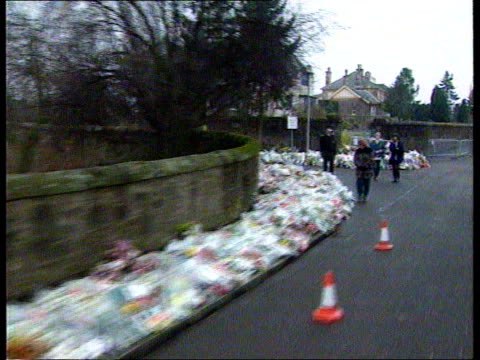 stockvideo's en b-roll-footage met firearms amnesty announced: father's appeal:; scotland: dunblane: ext lms track forward past floral tributes lining pavement leading to school r-l as... - crime and murder
