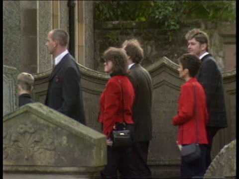 memorial service:; ext lms mcintosh and prince of wales towards out of cathedral: side people along thru graveyard r-l. - dunblane stock videos & royalty-free footage