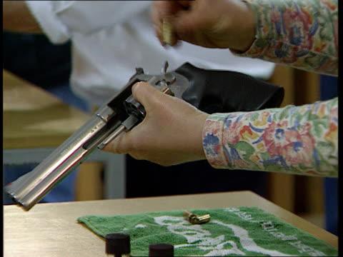preliminary hearing itn lib england london barnet cms hand loading bullets into rifle bv three people standing at firing positions at indoor shooting... - ダンブレーン点の映像素材/bロール