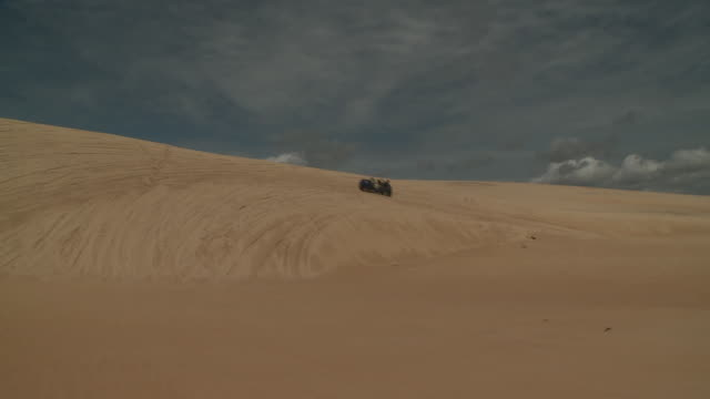 a dune buggy cruises over sand dunes. - dune buggy stock videos and b-roll footage