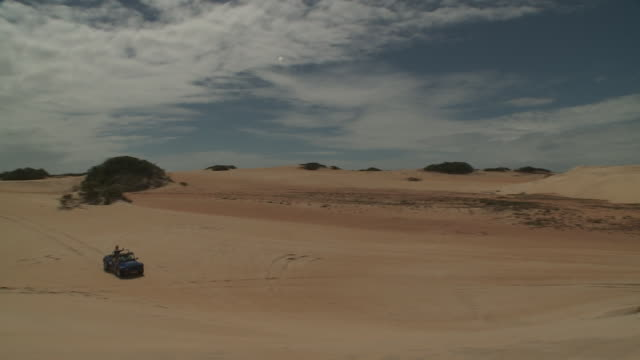 a dune buggy drives back and forth across a bowl shaped sand dune. - dune buggy stock videos and b-roll footage