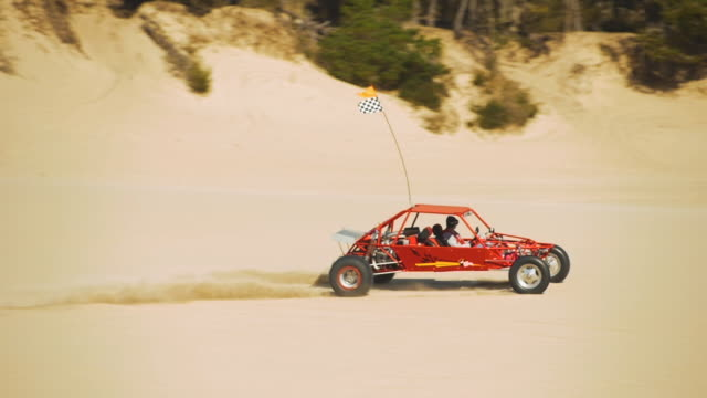 dune buggy driving on sand dunes in slow motion - dune buggy stock videos and b-roll footage