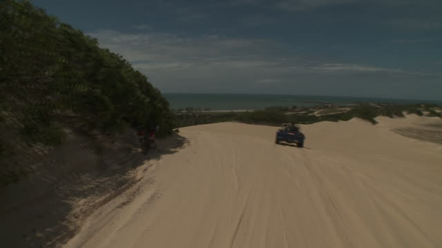 a dune buggy travels over sand past several hills covered in shrubs. - dune buggy stock videos and b-roll footage