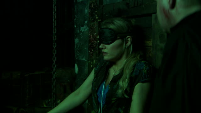 dungeon masters taunt a woman who sits blindfolded and tied to a chair. - dungeon stock videos & royalty-free footage