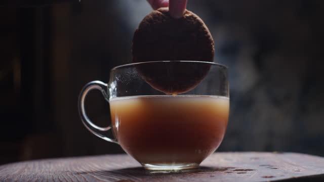 vídeos de stock, filmes e b-roll de mergulhando biscoito em masala chai - molhado