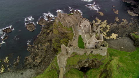 dunluce castle  - aerial view - northern ireland, united kingdom - northern ireland stock videos & royalty-free footage