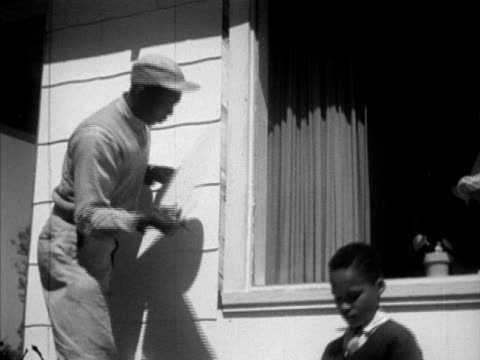 DuPont AfricanAmerican employee Manning Williams working on house w/ family son Ralph handing siding Wife Ada at door daughter Mary sweeping VS...
