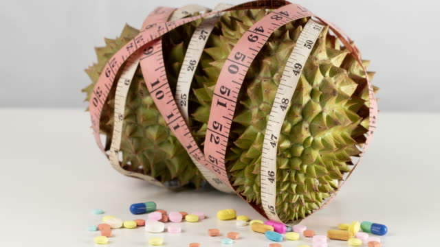 Durian, tablets, and measuring tape are placed on a white background.