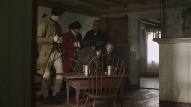 during a reenactment men dressed in colonial costumes talk and drink in a tavern. - colonial reenactment stock videos & royalty-free footage
