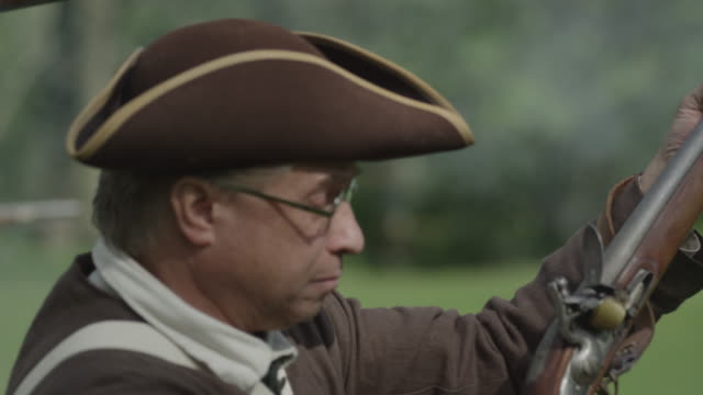 during a revolutionary war battle reenactment a soldier fires a musket and then runs with other soldiers across the field. - rifle stock videos & royalty-free footage