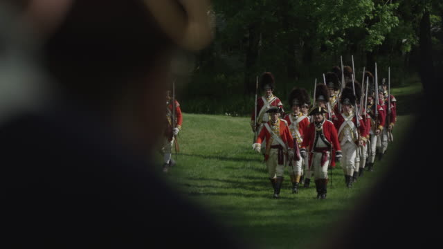 during a revolutionary war reenactment british grenadier soldiers march across a battlefield toward colonial soldiers. - revolution stock videos & royalty-free footage