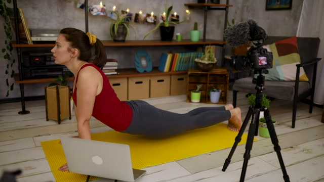 during covid-19 lockdown, yoga instructor using her free time and knowledge to record a yoga tutorial as her side hustle - side hustle stock videos & royalty-free footage