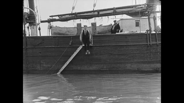 vídeos y material grabado en eventos de stock de 1923 during ship's deck chase, cabin boy (buster keaton) falls into the ocean - 1923