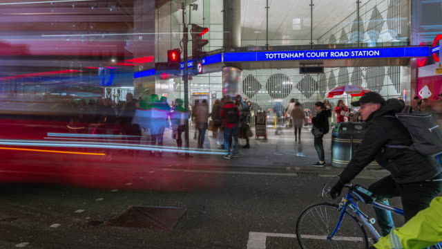 during the busy evening rush hour road traffic cyclists and pedestrians move rapidly past crossrails new station entrance at tottenham court road in the west end of london - investment stock videos & royalty-free footage