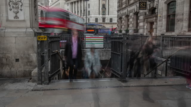 during the morning rush hour in the city of london a large number of commuters  rapidly flow out of a bank tube station exit with buses moving in the background - central london video stock e b–roll