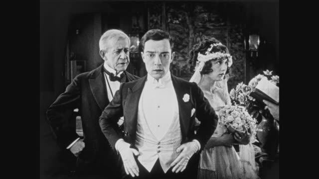 vídeos de stock, filmes e b-roll de 1920 during wedding ceremony, groom (buster keaton) realizes he's forgotten the wedding rings - aliança de casamento