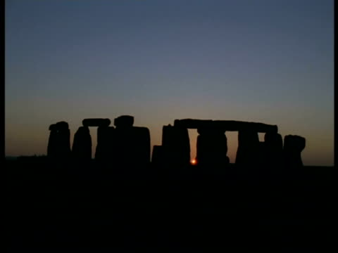 dusk and stonehenge - orange sun just visible between silhouetted stones, lilac/orange sky - stonehenge stock videos and b-roll footage