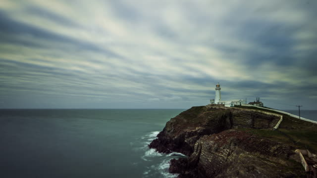 dusk at the south stack lighthouse on the island of anglesey north wales looking out to the irish sea with rapidly moving complex cloud layers above - wales stock videos & royalty-free footage