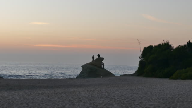 vídeos de stock, filmes e b-roll de dusk camel point, laguna beach young adults silhouetted against pale orange and blue sky climbing on a large rock young woman taking a selfie,... - oeste dos estados unidos