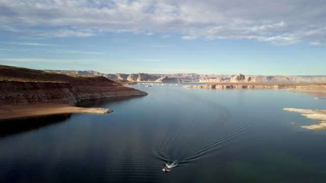 abenddämmerung drohne footage der lake powell mit anmutigen boot kreuzfahrt in wahweap bay - lake powell stock-videos und b-roll-filmmaterial