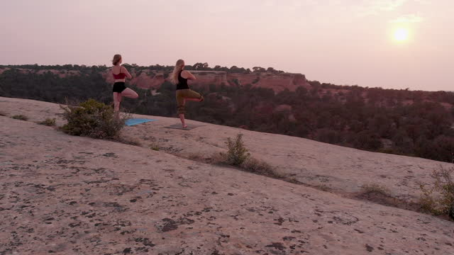 stockvideo's en b-roll-footage met dusk drone passing two women doing tree pose yoga on a large slab rock in the hills outside fruita colorado - in kleermakerszit