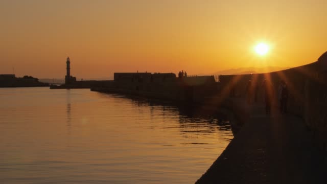 vídeos y material grabado en eventos de stock de dusk light over the harbour and the lighthouse silhouetted on the horizon, chania, crete, greece, europe - cultura mediterránea