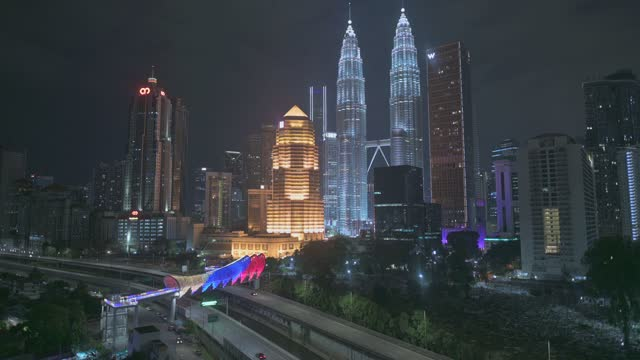 dusk pedestrian bridge lintasan saloma link between the old and new city of kuala lumpur - petronas twin towers stock videos & royalty-free footage