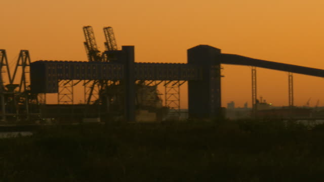 Dusk Rockingham CBH grain terminal camera pans along the plant stacks conveyor system leading to a cargo ship Repeated image