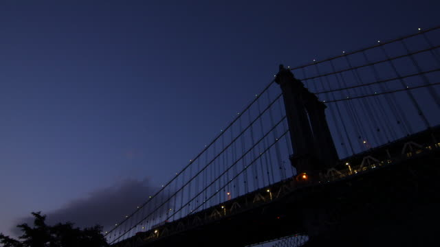 Dusk shot of a subway train running underneath the Brooklyn Bridge.