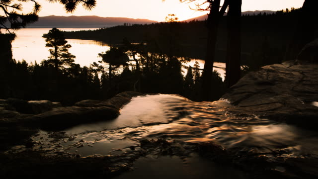 dusk shot of stream running into river above emerald bay, lake tahoe, california. - sunset bay state park stock videos & royalty-free footage