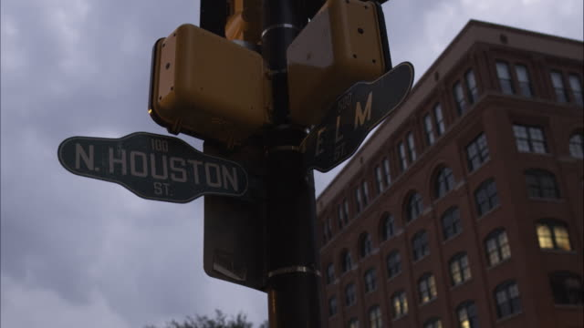 vídeos y material grabado en eventos de stock de dusk shot of the cross street sign n. houston st. and elm st. with the texas school book depository in the background. dealey plaza, dallas, texas. - señal de nombre de calle