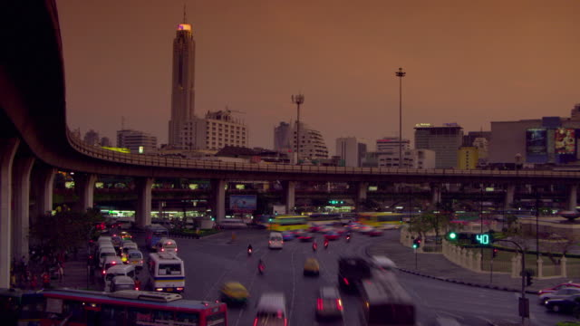 t/l ws ha dusk till night traffic at intersection with overpass and cityscape in background, bangkok, ayuthaya, thailand - see other clips from this shoot 1448 stock videos and b-roll footage