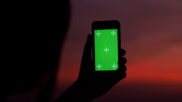 Dusk time of Silhouette woman using chroma key of smart phone with taking a picture of city scape