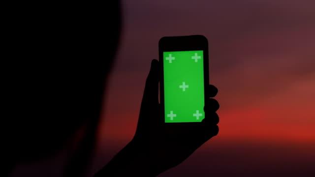 vídeos de stock, filmes e b-roll de tempo ao entardecer de mulher de silhueta usando croma de telefone inteligente com tirando uma foto de paisagem de cidade - showing